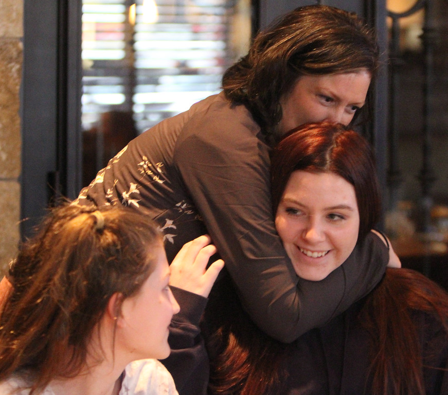 . Donna Rains of Somerville, who is being treated for a recurrence of breast cancer, is treated to a surprise makeover at Pyara Spa and Salon in Burlington, followed by lunch at Tuscan Kitchen. Rains hugs nieces Nina Savino, 12, left, and Mia Savino, 15, right, of Bridgewater, after arriving at lunch. (SUN/Julia Malakie)