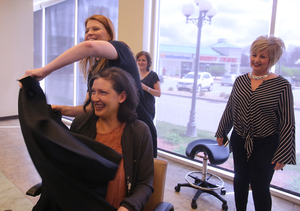 . Donna Rains of Somerville, who is being treated for a recurrence of breast cancer, is treated to a surprise makeover at Pyara Spa and Salon in Burlington, the first salon in Massachusetts participating in the Hello Gorgeous program. Rains reacts to her new haircut, as Pyara owner Christine Perkins of Lexington removes her bib [or whatever it\'s called]. At right is Ann Hudson from South Bend, Indiana, affiliate salon coach with Hello Gorgeous. (SUN/Julia Malakie)