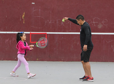 Alex Jovel of Lowell takes a break from hitting tennis balls against the wall at Shedd Park, to give his daughter Dalese, 6, a turn.  (SUN/Julia Malakie)