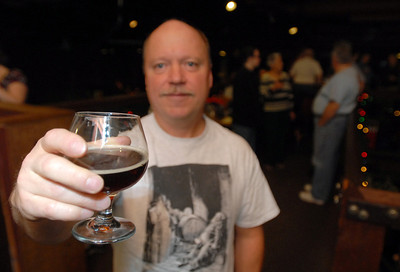 Tom Fitzpatrick of Batavia holds up a beer while enjoying the holiday party with members of the Urban Knaves of Grain home brewers' club at Two Brothers Roundhouse Wednesday Dec. 19, 2012. Tom was recently a finalist in the Sam Adams Home Brew Contest. Erica Benson—ebenson@shawmedia.com