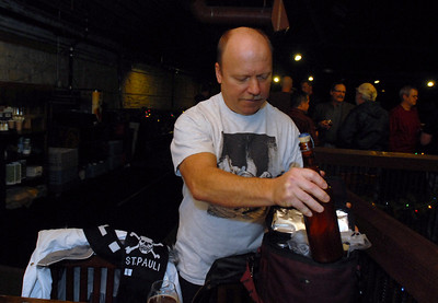 Tom Fitzpatrick of Batavia brings one of his home brewed beers to the holiday party with members of the Urban Knaves of Grain home brewers' club at Two Brothers Roundhouse Wednesday Dec. 19, 2012. Tom was recently a finalist in the Sam Adams Home Brew Contest. Erica Benson—ebenson@shawmedia.com