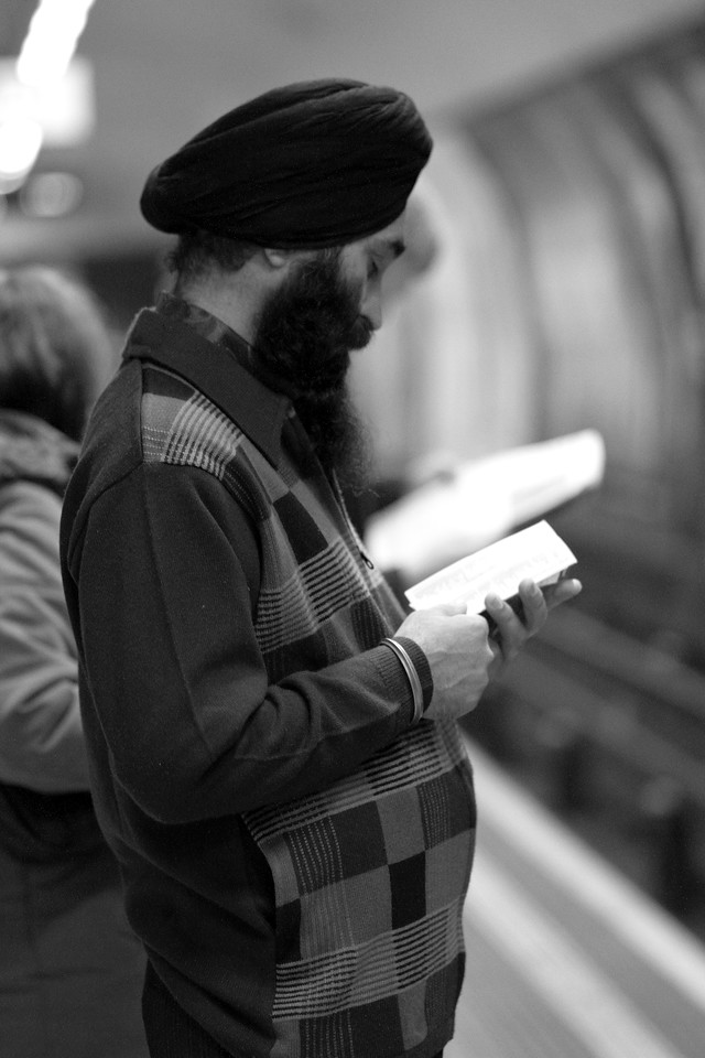 An Indian Man Reading While Waiting For the Underground Train