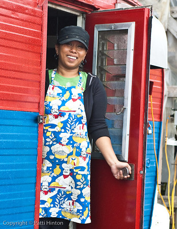 Sheila - Stranger #14 Sheila runs a chip wagon at our local farmers market. I was photographing her brightly coloured trailer when she popped her head out the door. A bit skeptical initially, she agreed to pose and asked if I liked the fresh paint job. I did.