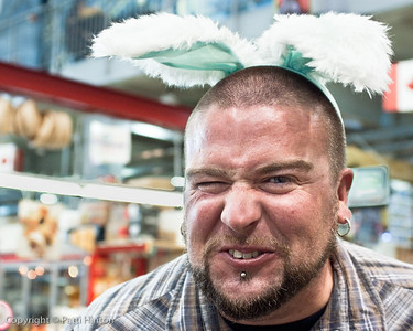 Joe - Stranger #1 April 9/09 How can you not work up your nerve to ask a punk Easter bunny for a photo? While at our local market I spotted this rather burly gent complete with studs wearing aqua fluffy bunny ears on Easter weekend. I had to have a shot of this. Joe was very accommodating about it and posed easily. As it turns out, he's a pro photographer here in town. Who knew? Thanks for being my first stranger, Joe.