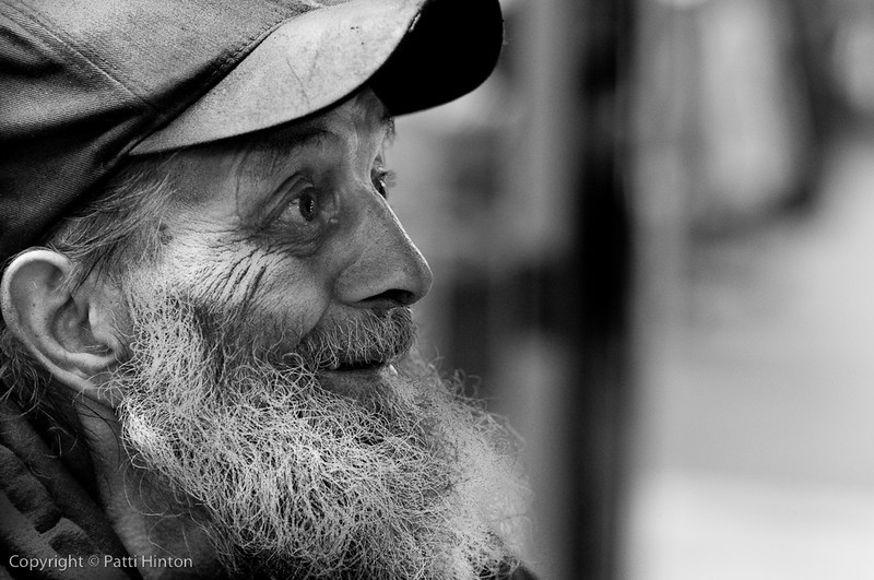 """J.C. 53/100  JC was chatting up passers-by in Dundas Square one evening. He was quite a character. When I asked for his name for the strangers project, he replied """"JC, short for """"justifiably crazy""""."""