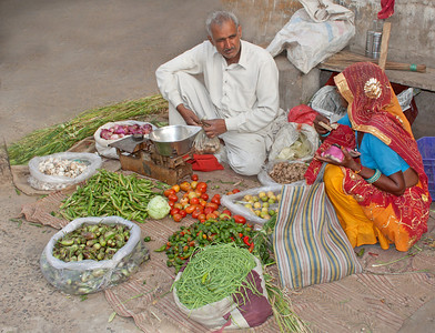 Grocer and customer on sidewalk, India