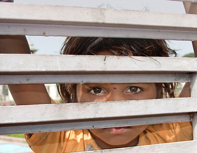 little girl looking through a gate - Delhi, India