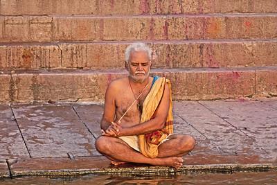 a man praying at the Ganges at sunrise