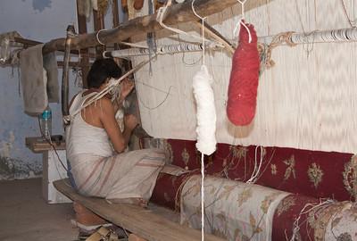 man weaving a carpet in India