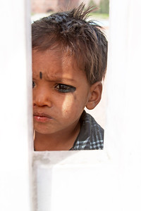 an Indian boy looking through a gate
