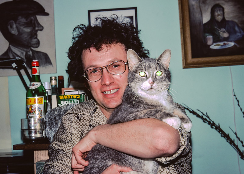 """Carl in his basement apartment surrounded by his drawings and hugging Puff: one of his long lived cats. Carl was a good friend for most of my adult life. During the many years I lived in Edmonton I spent a lot of time with Carl. It's rather odd that I have so few pictures of him. I have been an avid amateur photographer since I was eight but I only have half-a-dozen pictures of Carl. I held off """"developing"""" this image because of the reflection in Puff's eyes. Now I see this informal imperfection as a reflection, (pun intended), of Carl's haphazard fun filled way of life."""