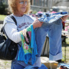 J-Mag/T. Rob Brown<br /> Opal Ward of Braggs, Okla., looks through a selection of clothes in the 600 block of Oak Ridge Drive in Neosho during the citywide garage sale Friday afternoon, April 5, 2013. Ward said her sister lives in Carl Junction and they like to come look at all the good deals.
