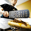 JMag/T. Rob Brown<br /> Philadelphia native David Stauffer, co-owner of On the Roll, adds the steak to a Philly cheesesteak sandwich Tuesday evening, Jan. 3, 2012, at the Duquesne business in Village Plaza on East 7th Street.