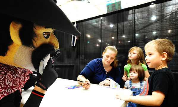 Globe/T. Rob Brown<br /> Angus, the Joplin Outlaws mascot, greets Garry Reynolds, 5, right, as Reynolds' mom, Renae Reynolds, of Joplin, signs him up for Miracle League of Joplin during area youth sports signup day at Missouri Southern State University's Leggett & Platt Athletic Center. His sisters Ruthann, 3, and Morgan, 6, look on.