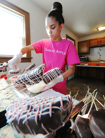 J-Mag/T. Rob Brown<br /> Ana Stuhlman, 14, with Carmen's Apples, decorates chocolate-covered fruits Thursday morning, July 18, 2013, in the family's home kitchen.