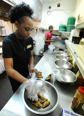 J-Mag/T. Rob Brown<br /> Jacqueline Hackett, co-owner of Hackett Hot Wings, finishes up an order of the restaurant's famous Caribbean Jerk dry rub Wednesday afternoon, July 3, 2013.