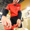 J-Mag/T. Rob Brown<br /> Owner Tom Hamsher ties a ribbon on a giant candy cane at Minerva Candy in Webb City.
