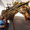 J-Mag/T. Rob Brown<br /> Brady Wilson, a Columbia Elementary School third grader, peers under a horse at Spiva Center for the Arts Tuesday afternoon, Jan. 31, 2012. Students on a field trip visited the gallery to see Rachel Wilson's found wood sculptures of horses and other horse-themed art pieces such as collages, etchings and monoprints.