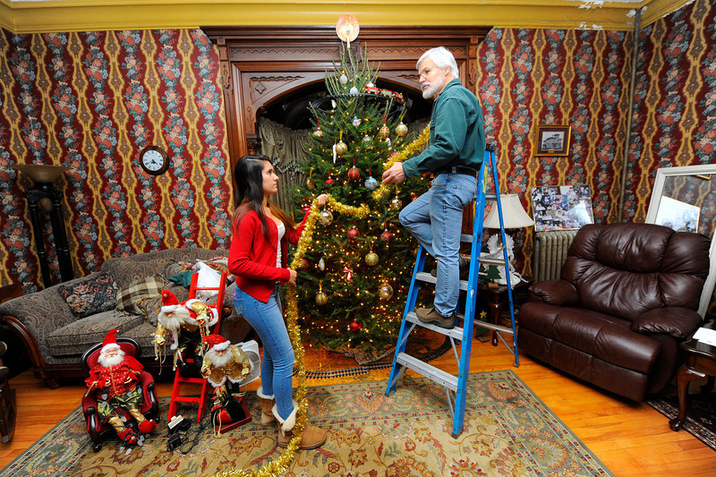 Homeowner Jack Hoover and his daughter Shannon Hoover, 14, decorate their Christmas tree on Thursday. Hoover will be hosting his 9th annual open house Toys for Tots fundraiser at his home, the Whitney House, at 127 Merriam Ave. in Leominster on December 13th from 7 p.m. to 9 p.m.<br /> SENTINEL & ENTERPRISE / BRETT CRAWFORD