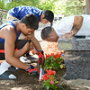 Brandon (left) and Sixto (center) Oliver, brothers of Jeremiah Oliver, as well as Jeremiah's father Jose (right), plant flowers surrounding the new bench in the 5-year-old's honor at Coggshall Park in Fitchburg on Saturday afternoon. SENTINEL & ENTERPRISE / Ashley Green