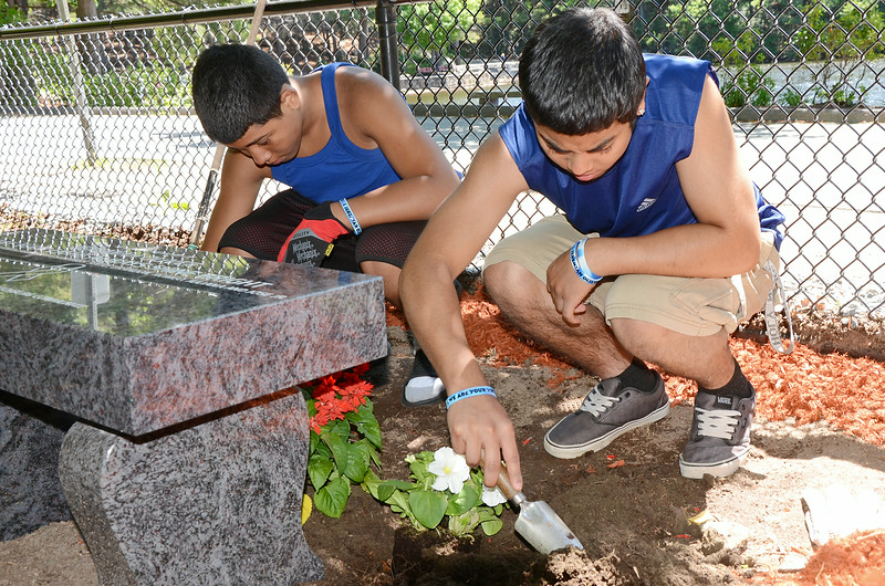 Brandon (left) and Sixto (right) Oliver, brothers of Jeremiah Oliver, plant flowers surrounding the new bench in the 5-year-old's honor at Coggshall Park in Fitchburg on Saturday afternoon. SENTINEL & ENTERPRISE / Ashley Green