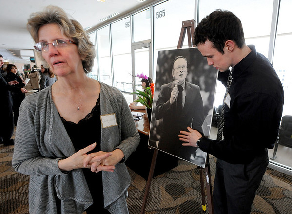"""Sandy Quiller, wife of Jerry Quiller, waits for guests with her son, Robb, who is next to a photo of his father.<br /> A memorial service was held at the Byron R. White Stadium Club for former University of Colorado track and field coach, Jerry Quiller. Quiller, who coached at CU from 1985 to 1995, died of cancer at age 69  on February 2, 2012.<br /> For more photos of the memorial, go to  <a href=""""http://www.dailycamera.com"""">http://www.dailycamera.com</a>.<br /> February 11, 2012 / Cliff Grassmick"""