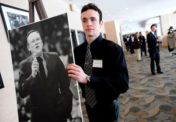 """Robb Quiller moves a photo of his father to the greeting area of the memorial service.<br /> A memorial service was held at the Byron R. White Stadium Club for former University of Colorado track and field coach, Jerry Quiller. Quiller, who coached at CU from 1985 to 1995, died of cancer at age 69  on February 2, 2012.<br /> For more photos of the memorial, go to  <a href=""""http://www.dailycamera.com"""">http://www.dailycamera.com</a>.<br /> February 11, 2012 / Cliff Grassmick"""