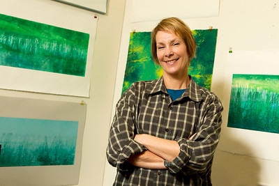 "Lonnie Harvey calls herself a printmaker. Technically, this is true. The walls of her studio are lined with prints, each depicting a single snippet of the natural world—ears of corn, milkweed, water, leaves, brooding open sky—imagery one might expect to find wandering bucolic Concord or nearby Carlisle, where the artist lives. Yet there is a looseness and painterly quality to Harvey's work, a spontaneity from one piece to the next, that makes ""printmaker"" feel more like a misnomer than accurate descriptor.     Take the corn for example. A grid of four prints is pinned to the studio wall, each containing the same image: two pieces of corn lying parallel to one another, wrinkled husks still intact. The first image in the series is vivid and crisp, warm and brightly colored and full of detail, the husks standing out in bright yellow relief. The image next to it, though still containing the same objects, is foggy and muted, its palette cool, an impression more than anything else. Beneath it lays another ghostly image, this one highlighting the ears of corn alone, the husks all but buried under a streaky haze.     Though the prints contain the same imagery, it is abundantly clear that each is markedly different than the one before it. This is in stark contrast to most forms of printmaking, in which multiples of the exact same image are reproduced again and again. Instead, Lonnie Harvey's prints have more in common with painting; each print is a one-of-a-kind piece.     Harvey's technique is known as monoprinting. ""They are called painterly prints because you paint onto Plexiglas and then print that image onto paper,"" the artist explains. This differs from other printmaking techniques in which an image is permanently affixed to a plate, such as a woodcut or engraving. Instead, Harvey explains, ""When you take the paper off, there might be something left on the glass, but it's not the same image. That's why it's called a 'monoprint'.""   Because she is working from glass or mylar, another non-permanent base material, the image is transient, and invites fluidity to the artist's process. Often, Harvey begins with her own photographs of nature taken as she goes about her day-to-day. She transfers these photographs onto the plate with ink before going in with a paintbrush or some other tool and modifying the image. This offers the best of both worlds, the precision of a real-life recording along with the ability to expound upon the idea with her own marks drawn freehand with a vibrant and startling combination of colors.     It is precisely this that has held the artist's attention for over two decades. A Wisconsin native, Harvey earned a degree in fine arts from the University of Wisconsin, Madison before taking up watercolor and heading east to Massachusetts. Here she realized watercolor was too unforgiving a medium for her—""too precise""—and decided to take a monoprinting class on a whim.     Twenty years later, the attraction holds strong. ""Some of it can be predictable, some of it is not. And I like that part of it. I know I can get a certain effect, but it's not going to be exact. Which is what monoprinting is. That's the best part—pulling that paper off. That's the part that will always keep me going with it—the unpredictability. I love it."""