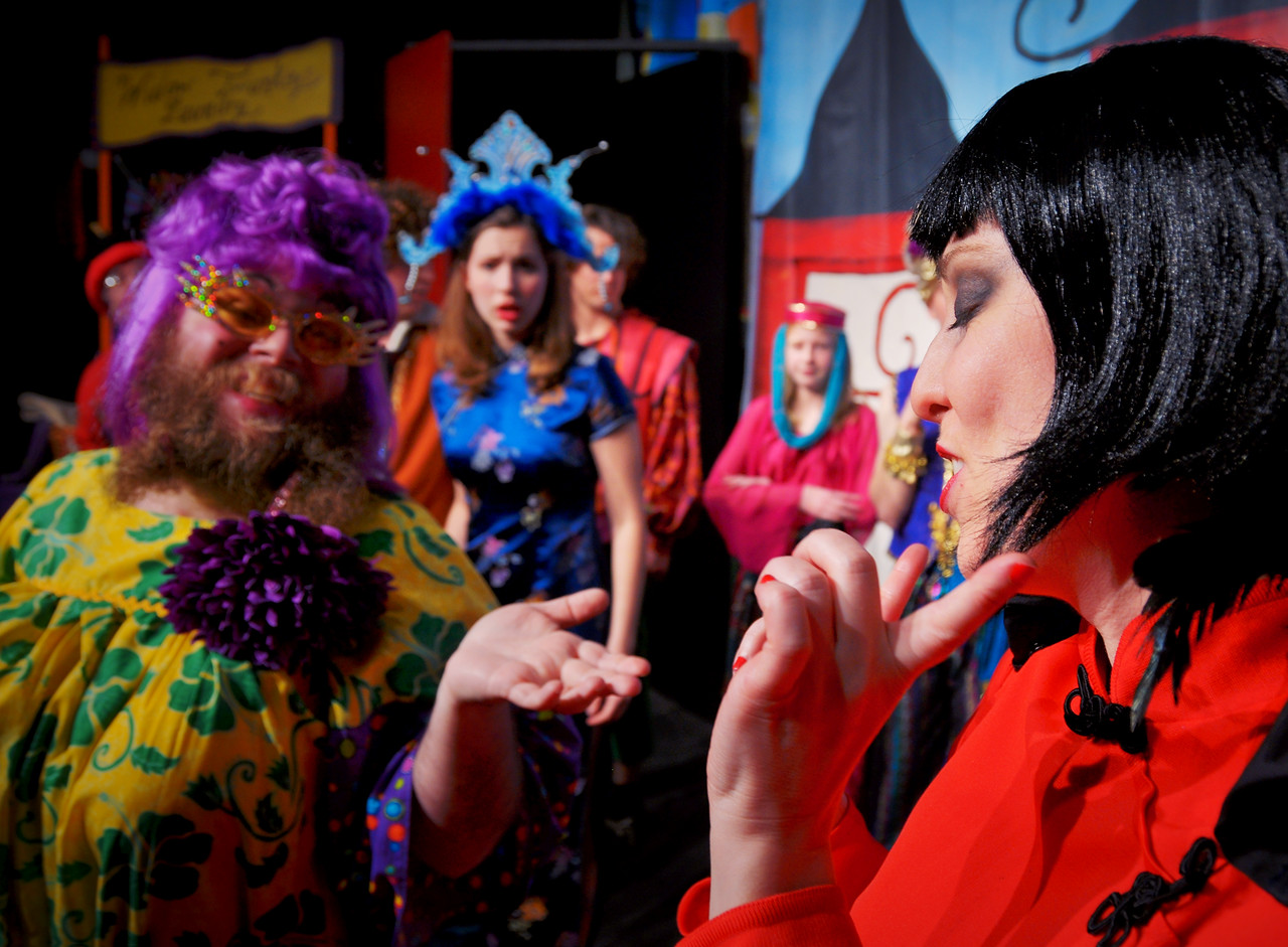 The Widow Twankey discusses the matter of a dowry with the Empress while the Princess and her retinue look on.<br /> Visible L to R: Michael Smith, Jonathan Dietrich, Spencer Padfield, Marijana Vorkapic, Adam Cyr, Allison Wilson, Melanie Card