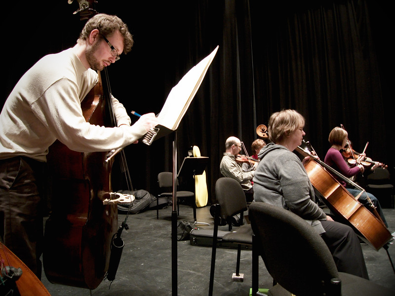 Principal Bass Ian Whitman makes notes on sheet music during rehearsals of Kitchener-Waterloo Symphony.   Image # KWS005