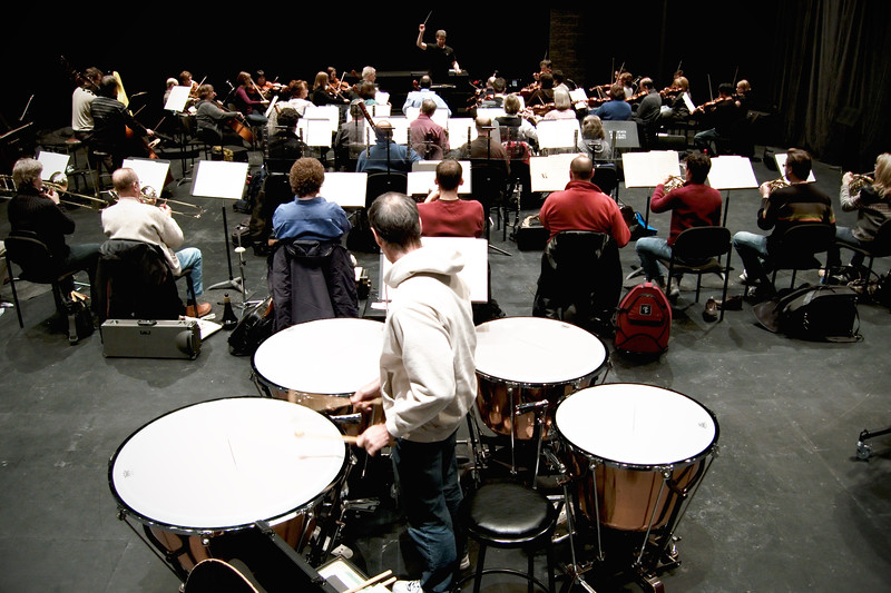 Kitchener Waterloo Symphony during rehearsal.  Deep perspective shot from rear; timpani in foreground, conductor Edwin Outwater at rear.   Image # KWS004
