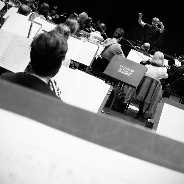 Edwin Outwater conducts the Kitchener-Waterloo symphony in rehearsal.  Angled horizon, deep perspective shot with editorial allowance at bottom.  B&W rendering.  Image # KWS001