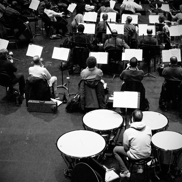 Rear ranks of Kitchener Waterloo Symphony during rehearsal.  Crane shot featuring timpani, brass and woodwinds.  B&W rendering. Image # KWS003
