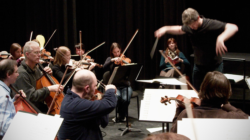 Edwin Outwater conducts the Kitchener Waterloo Symphony during rehearsal.  Action shot with string players.   Image # KWS008
