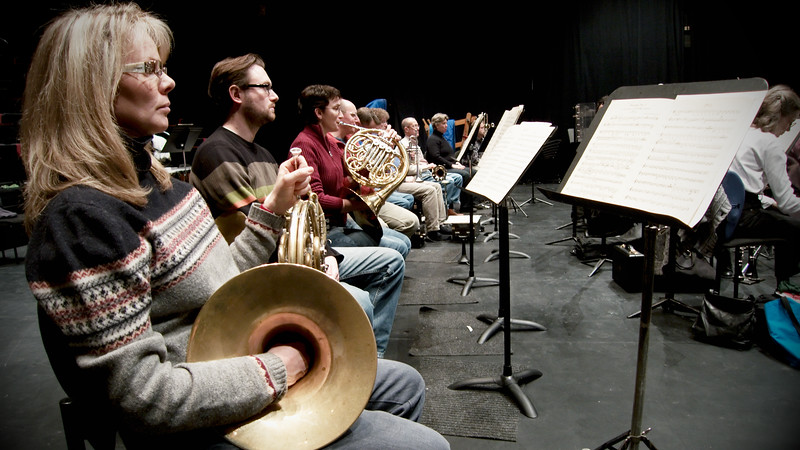 Brass section of Kitchener-Waterloo Symphony during rehearsal.  Musician names TBA.  Deep perspective shot down a row. Image # KWS002