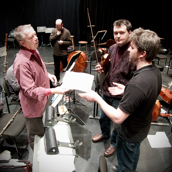 Principal Flutist Thomas Kay (left) and Concertmaster Stephen Sitarski (right centre) consult with Musical Director Edwin Outwater (right) during rehearsals of the Kitchener-Waterloo Symphony.   Image # KWS007