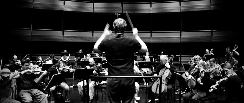 Music Director Edwin Outwater conducts members of the Kitchener-Waterloo Symphony during dress rehearsals at Centre in the Square.  B&W long torso rear action shot with players in the background.