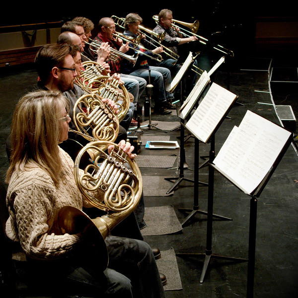 Looking down a row of horns, trumpets and trombones during rehearsals for the Kitchener-Waterloo Symphony.  Musicians from left to right: Horn Deborah Stroh, Horn (name?), Horn (name?), Principal Horn Martin Limoges, Principal Trumpet Larry Larson, Trumpet Daniel Warren, Principal Trombone Jay Castello, Trombone Rachel Thomas, Bass Trombone Doug Lavell (verify).  Perspective shot.