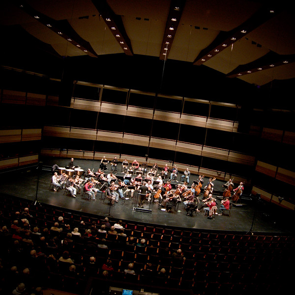The Kitchener-Waterloo Symphony conducted by Music Director Edwin Outwater during an open dress rehearsal at the Centre in the Square. Wide angle tilt horizon survey shot emphasising architectural details of the hall.