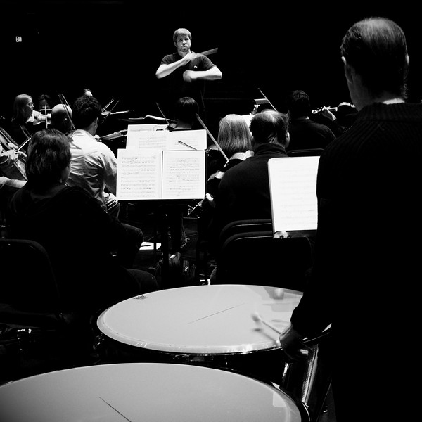 Music Director Edwin Outwater conducts members of the Kitchener-Waterloo Symphony during rehearsals.  B&W deep perspective shot looking over the shoulder of Principal Timpani Ron Brown.