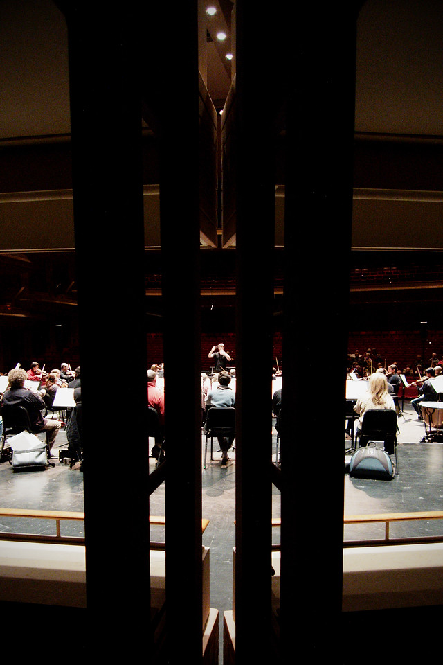 The Kitchener-Waterloo Symphony conducted by Music Director Edwin Outwater during an open dress rehearsal at the Centre in the Square.  Creative shot featuring obscurative pillars.