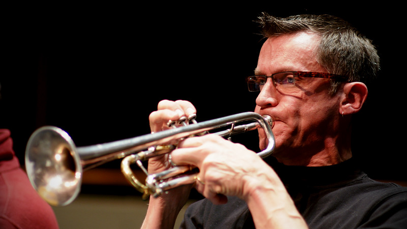 Principal Trumpet Larry Larson during rehearsal for the Kitchener-Waterloo Symphony.  Close-up, action portrait.
