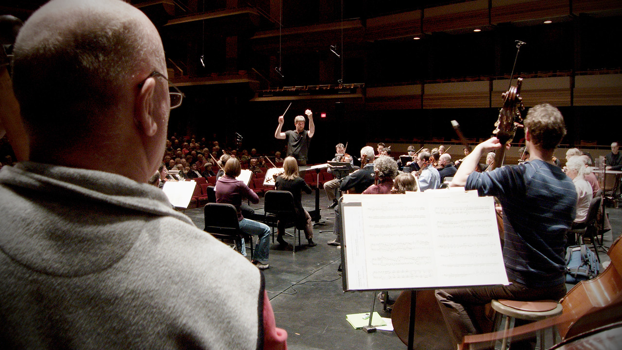 Looking over the shoulder of Asst. Principal Bass Milos Petrak towards the conductor's podium where Music Director Edwin Outwater conducts during an open dress rehearsal for the Kitchener-Waterloo Symphony.  Deep perspective, wide angle shot.