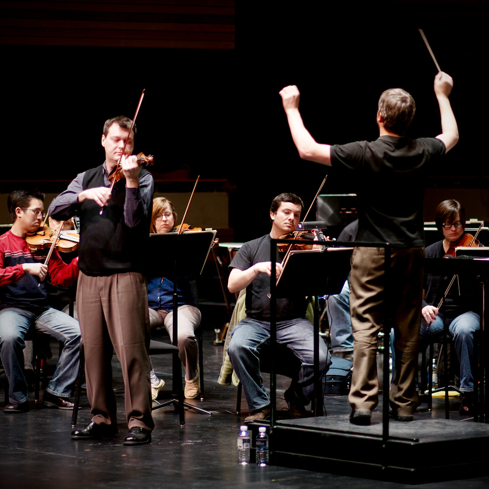 Music Director Edwin Outwater conducts violin soloist Stephen Sitarski during rehearsals for the Kitchener-Waterloo Symphony.  Telephoto action shot.