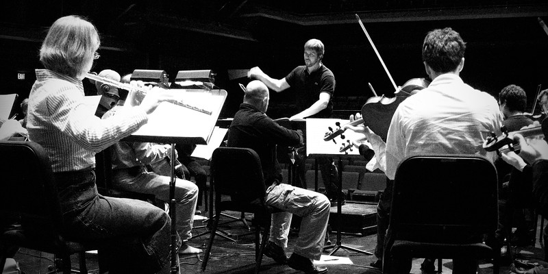 Music Director Edwin Outwater conducts members of the Kitchener-Waterloo Symphony during rehearsals.  B&W wide angle shot featuring violas and flute.