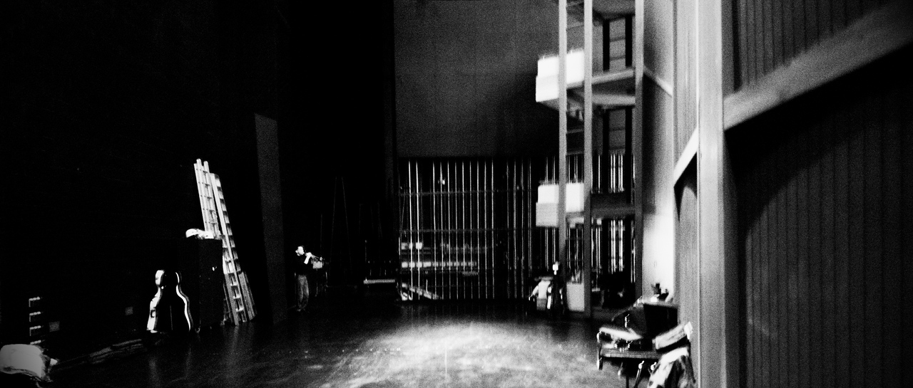 Principal Trumpet Larry Larson plays behind the stage at the Centre in the Square during rehearsals for the Kitchener-Waterloo Symphony.  Creative long exposure B&W wide angle.