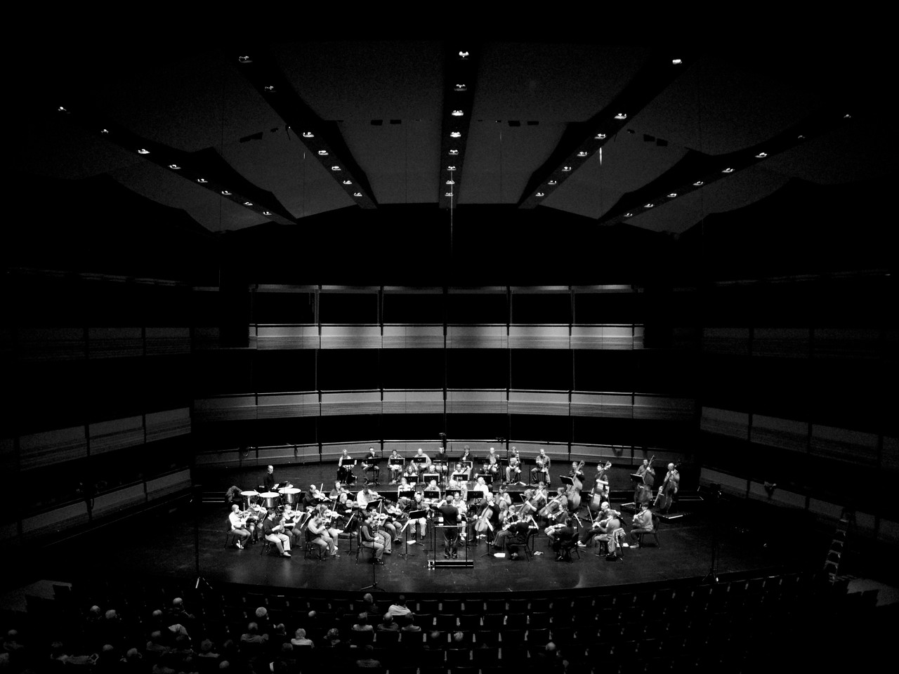 The Kitchener-Waterloo Symphony conducted by Music Director Edwin Outwater during an open dress rehearsal at the Centre in the Square. B&W wide angle survey shot emphasising architectural features of the hall.