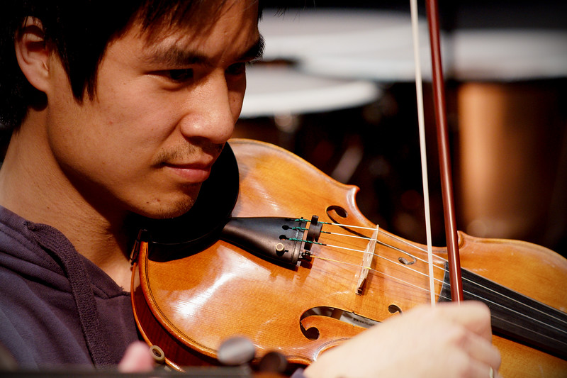 First Violin (name?) plays during rehearsal for the Kitchener-Waterloo Symphony.  Close-up action portrait.