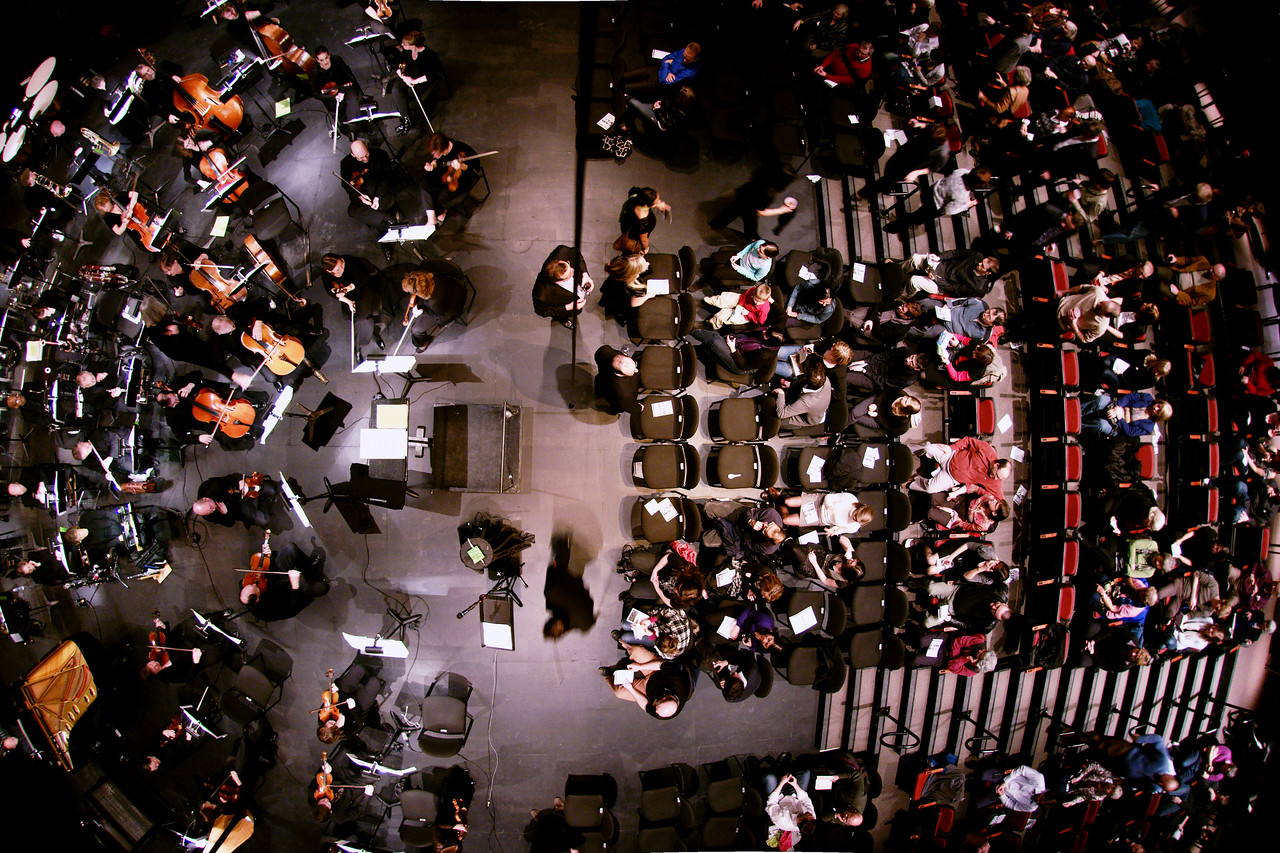 Overhead view of the orchestra and patrons as Concertmaster Stephen Sitarski takes his position at the head of the first violins.