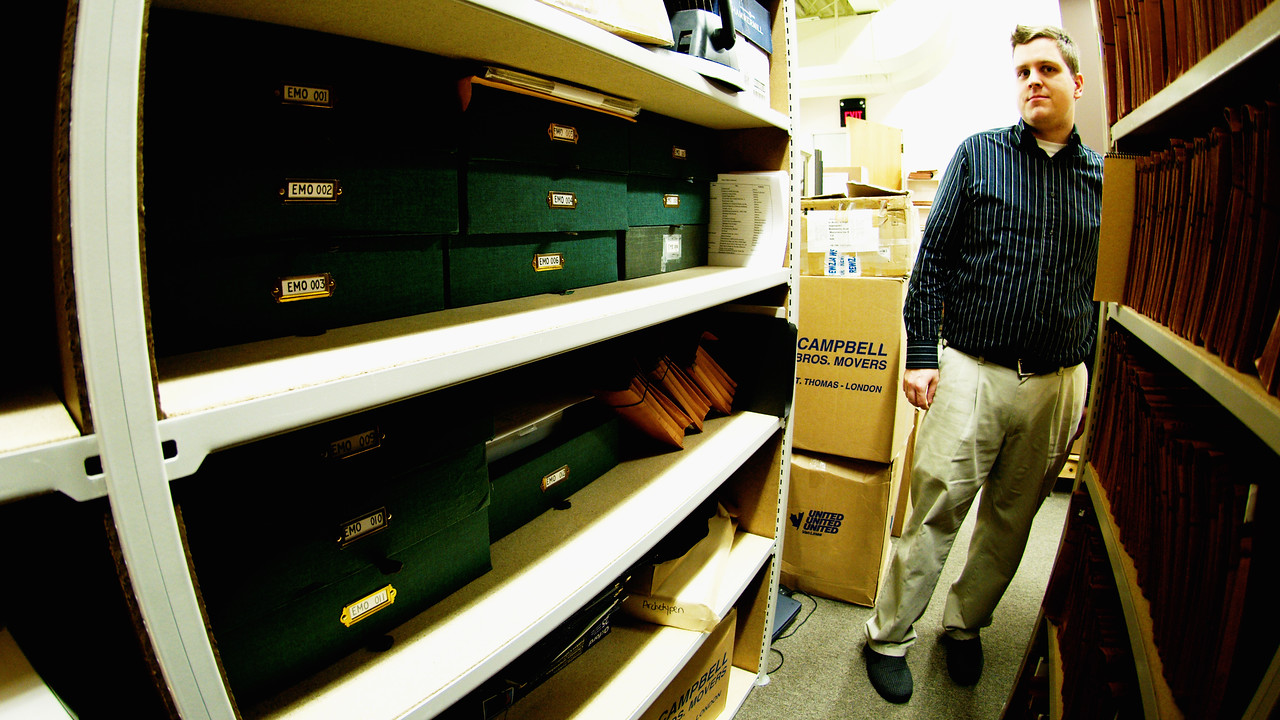 "KWS librarian Corey Rempel in the ""stacks"" of folders and boxes that hold the KW Symphony's musical library.  The green boxes on the left marked EMO are Music Director Edwin Outwater's personal files."